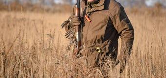 Vogel Hunter Silhouetted bij Zonsopgang met dode vogel op zijn hand stock foto's