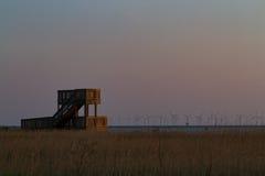 Vogelbeobachtungsplatz und -windmühlen im Horizont Lizenzfreie Stockfotos