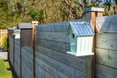 Vogelhäuser auf einer Reihe an einem Zaun Stockbild