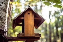 Vogelhaus mit unscharfer Natur im Hintergrund stockbilder