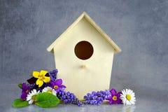 Vogelhaus- und -frühlingsblumen Lizenzfreies Stockfoto