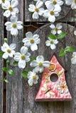 Vogelhuis op oude houten omheining met kornoeljes stock foto