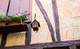 Vogelhuis van het venster van een oud huis met stralen wordt opgeschort die Stock Fotografie