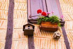 Vogelhuis van het venster van een oud huis met stralen wordt opgeschort die Stock Foto's