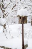 Vogelhuiszitting bovenop een pool en behandeld met sneeuw royalty-vrije stock afbeeldingen