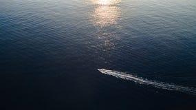 Vogelmening van een kleine vissersboot op de kalme overzeese golf, geschotene zonsondergangtijd stock foto's
