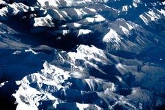 Vogelperspektive über den felsigen Bergen vom Flugzeug Stockfotos