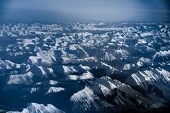 Vogelperspektive über den felsigen Bergen vom Flugzeug Stockbild