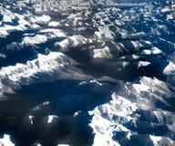 Vogelperspektive über den felsigen Bergen vom Flugzeug Lizenzfreie Stockfotos