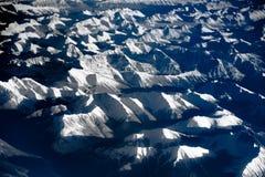 Vogelperspektive über den felsigen Bergen vom Flugzeug Lizenzfreie Stockfotografie