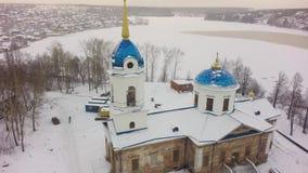 Vogelperspektive über weißer Kirche im Winter während der starken Schneefälle Vogelperspektive der Kirche in Russland clip Kleins stock footage