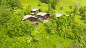 Vogelperspektive, alpine Chalets auf grünem Berghang unter blauem s Stockfoto