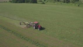 Vogelperspektive auf dem Landwirtschaftstraktor, der an großem Feld, Erntemaschine auf Feld, rote Traktorfunktion auf dem Feld a stock video footage