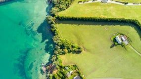 Vogelperspektive auf einem Ackerland auf dem Ufer des sonnigen Hafens Whangaparoa-Halbinsel, Auckland, Neuseeland Stockfotografie