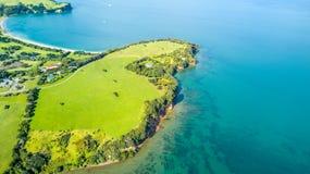 Vogelperspektive auf einem Ackerland auf dem Ufer des sonnigen Hafens Whangaparoa-Halbinsel, Auckland, Neuseeland Lizenzfreie Stockbilder