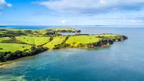 Vogelperspektive auf einem Ackerland auf dem Ufer des sonnigen Hafens Whangaparoa-Halbinsel, Auckland, Neuseeland Stockbilder
