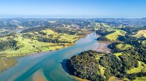 Vogelperspektive auf einem Fluss, der durch Ackerland mit Wald und grasartigen Wiesen läuft Auckland, Neuseeland Stockbilder