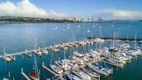 Vogelperspektive auf einem Jachthafen und stillstehenden Booten mit Auckland-Stadtzentrum auf dem Hintergrund Irgendwo in Neuseel Stockbild