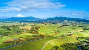 Vogelperspektive auf einem Straßenlauf durch Ackerland mit Berg Taranaki auf dem Hintergrund Taranaki-Region, Neuseeland Stockbild