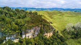 Vogelperspektive auf einer felsigen Klippe mit Wald und Ackerland auf dem Hintergrund Taranaki-Region, Neuseeland Lizenzfreies Stockfoto