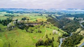 Vogelperspektive auf einer felsigen Klippe mit Wald und Ackerland auf dem Hintergrund Taranaki-Region, Neuseeland Lizenzfreie Stockfotos