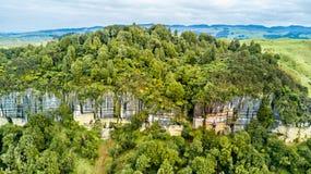 Vogelperspektive auf einer felsigen Klippe mit Wald und Ackerland auf dem Hintergrund Taranaki-Region, Neuseeland Lizenzfreie Stockfotografie