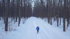 Vogelperspektive auf glücklichem Mädchen, das um die Schneewehen in der Waldszenischen Winterlandschaft läuft stock footage