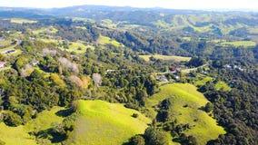 Vogelperspektive auf grünen Hügeln mit Wohnhäusern Irgendwo in Neuseeland Stockbild