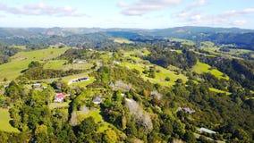 Vogelperspektive auf grünen Hügeln mit Wohnhäusern Irgendwo in Neuseeland Lizenzfreie Stockfotos