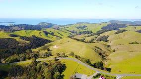 Vogelperspektive auf grünen Hügeln mit Wohnhäusern mit schönem Hafen auf dem Hintergrund Irgendwo in Neuseeland Lizenzfreies Stockfoto