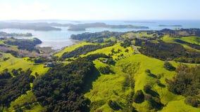 Vogelperspektive auf grünen Hügeln mit Wohnhäusern mit schönem Hafen auf dem Hintergrund Irgendwo in Neuseeland Lizenzfreie Stockbilder