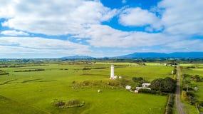 Vogelperspektive auf Kap Egmont-Leuchtturm mit Ackerland auf dem Hintergrund Taranaki-Region, Neuseeland Lizenzfreie Stockbilder