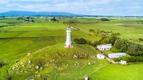 Vogelperspektive auf Kap Egmont-Leuchtturm mit Ackerland auf dem Hintergrund Taranaki-Region, Neuseeland Lizenzfreies Stockbild