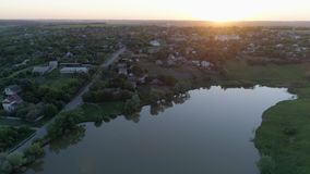 Vogelperspektive auf Kleinstadt nahe See bei Sonnenuntergang am Frühling stock video