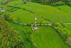 Vogelperspektive auf Stahltelekommunikationsturm im grünen Land mit Wiese, Wald und Dorf lizenzfreie stockfotos