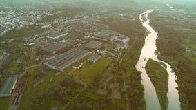 Vogelperspektive der überraschenden Stadtlandschaft und ein beträchtliches von grauen Gebäuden, nah an geschlängeltem Fluss 4K stock footage