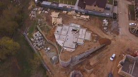 Vogelperspektive der Baustelle laufend nahe neuen modernen Häuschen, Baumaterialien und dem Arbeitskraftgießen stock video