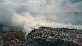 Vogelperspektive der brennenden Müllkippe die Umwelt verunreinigend Starker Wind steigt giftiger Rauch des brennenden Abfalls in stock footage