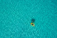 Vogelperspektive der dünnen Frauenschwimmens auf dem Schwimmenringdonut im transparenten Türkismeer in Seychellen Sommermeerblick lizenzfreies stockfoto