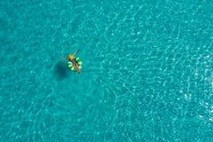 Vogelperspektive der dünnen Frauenschwimmens auf dem Schwimmenringdonut im transparenten Türkismeer in Seychellen Sommermeerblick lizenzfreie stockfotografie