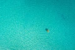Vogelperspektive der dünnen Frauenschwimmens auf dem Schwimmenringdonut im transparenten Türkismeer in Seychellen Sommermeerblick stockfoto