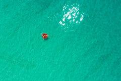 Vogelperspektive der d?nnen Frauenschwimmens auf dem Schwimmenringdonut im transparenten T?rkismeer in Seychellen Sommermeerblick stockbild