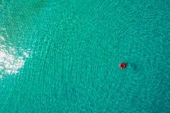 Vogelperspektive der d?nnen Frauenschwimmens auf dem Schwimmenringdonut im transparenten T?rkismeer in Seychellen Sommermeerblick lizenzfreies stockbild