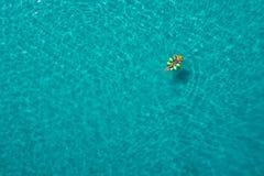 Vogelperspektive der d?nnen Frauenschwimmens auf dem Schwimmenringdonut im transparenten T?rkismeer in Seychellen Sommermeerblick lizenzfreie stockfotos