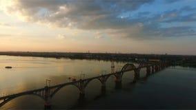 Vogelperspektive der Eisenbahnbrücke über dem Dnieper-Fluss Die Stadt von Dnipro Dnepropetrovsk Schießen während eines schönen So stock footage