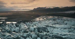 Vogelperspektive der Eislagune auf Sonnenuntergang Hubschrauber, der über den Gletscher Vatnajokull mit vulkanischer Asche in Isl stock video