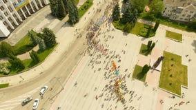 Vogelperspektive der ernsten Parade der Tanzgruppen, die entlang Hauptstraßen der Stadt entlang dem Damm zu marschieren stock footage