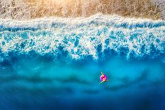 Vogelperspektive der Frauenschwimmens auf dem rosa Schwimmenring im Meer Lizenzfreie Stockbilder
