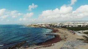 Vogelperspektive der Küstenlinie mit einsamen Strand- und Stadtbergen im Hintergrund Starke stürmische Wellen, die sandigen Stran stock footage