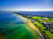 Vogelperspektive der Küstenlinie setzt nahe Elwood mit Melbourne CBD auf den Strand Stockfotos